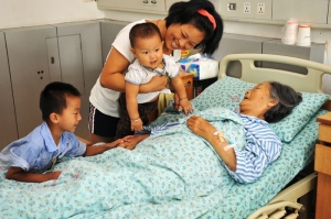 Image: Lou Xiaoying, right, lies in the hospital with one of her daughters, center.